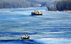 A U.S. Coast Guard boat (L) and a barge being pushed by a tug boat navigate the icy waters of the Hudson River in Stuyvesant, N.Y., on Thursday. (AP Photo/Mike Groll)