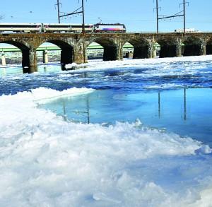 A New Jersey transit passenger train crosses a bridge over the partially frozen Delaware River near Trenton, N.J., Thursday. (AP Photo/Mel Evans)