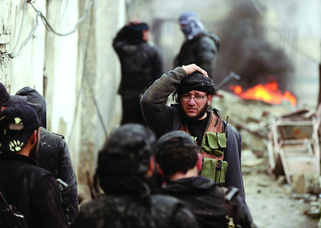 An injured Free Syrian Army fighter holds his head soon after a tank shell exploded on a wall during heavy fighting in the Ain Tarma neighborhood of Damascus on Wednesday. ( REUTERS/Goran Tomasevic)