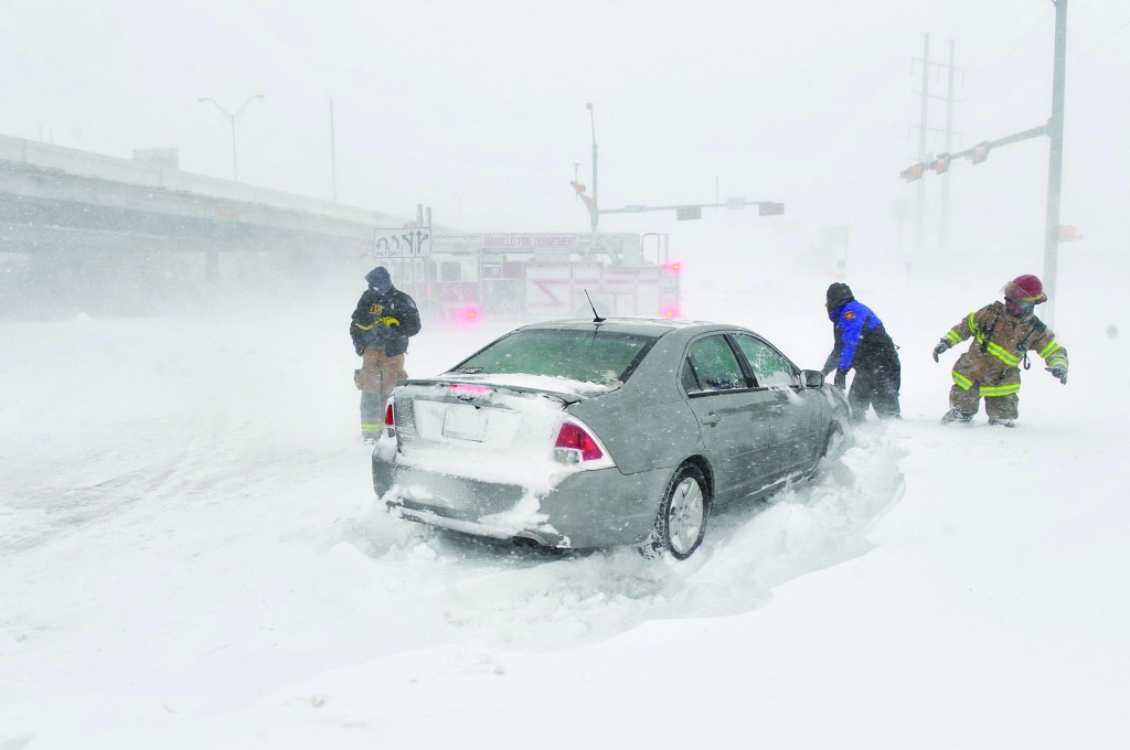 Amarillo emergency personnel assist a stranded motorist on the I-40 service road Monday. Interstate 40 and many major highways in the Panhandle have been closed. (AP Photo/The Amarillo Globe News,Michael Schumacher)