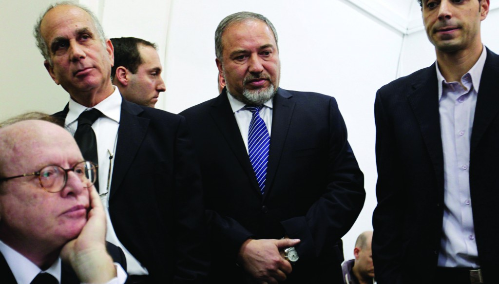 Avigdor Lieberman (C), former Israeli foreign minister, waits in the courtroom before the opening hearing of his trial in Yerushalayim on Sunday. (REUTERS)