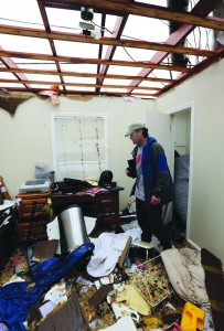 Charlie Ramp looks for personal items at his damaged home in Hattiesburg, Miss., Monday, after a tornado damaged the area Sunday afternoon. (AP Photo/Chuck Cook)