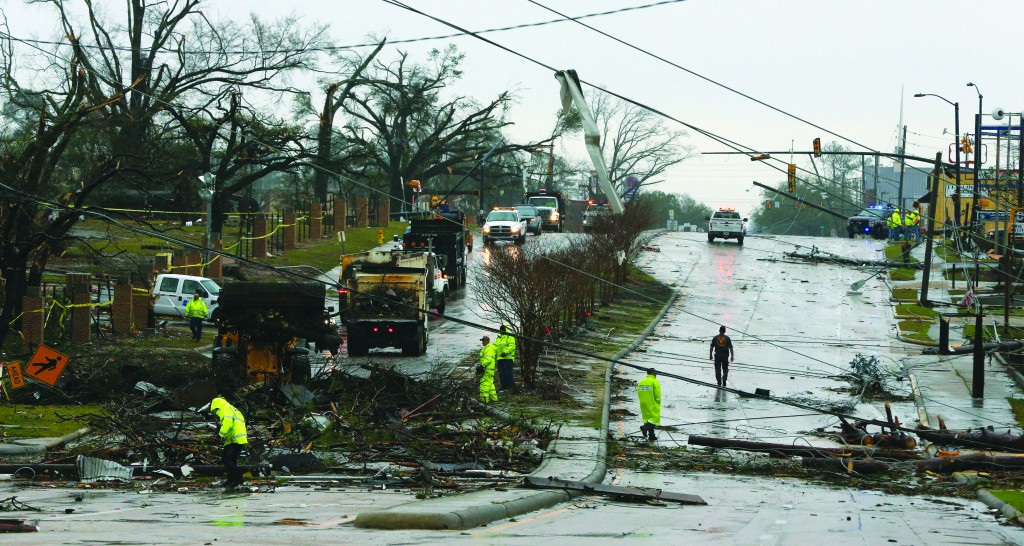 Workers clear debris from Hardy Street in front of the University of Southern Mississippi in Hattiesburg, Miss., Monday, after a tornado ripped through the area Sunday afternoon. The powerful twister tore a path across at least three counties, injuring more than 60 people — but killing none. (AP Photo/Chuck Cook)