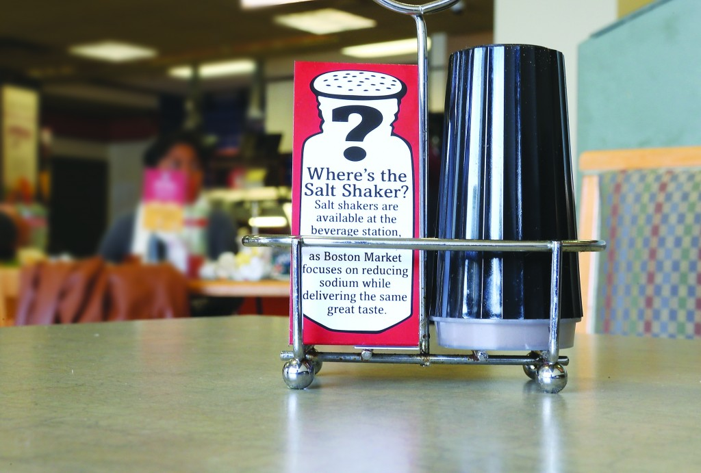 A sign explaining the absence of salt shakers is posted on a table inside a California restaurant. (Justin Sullivan/Getty Images)