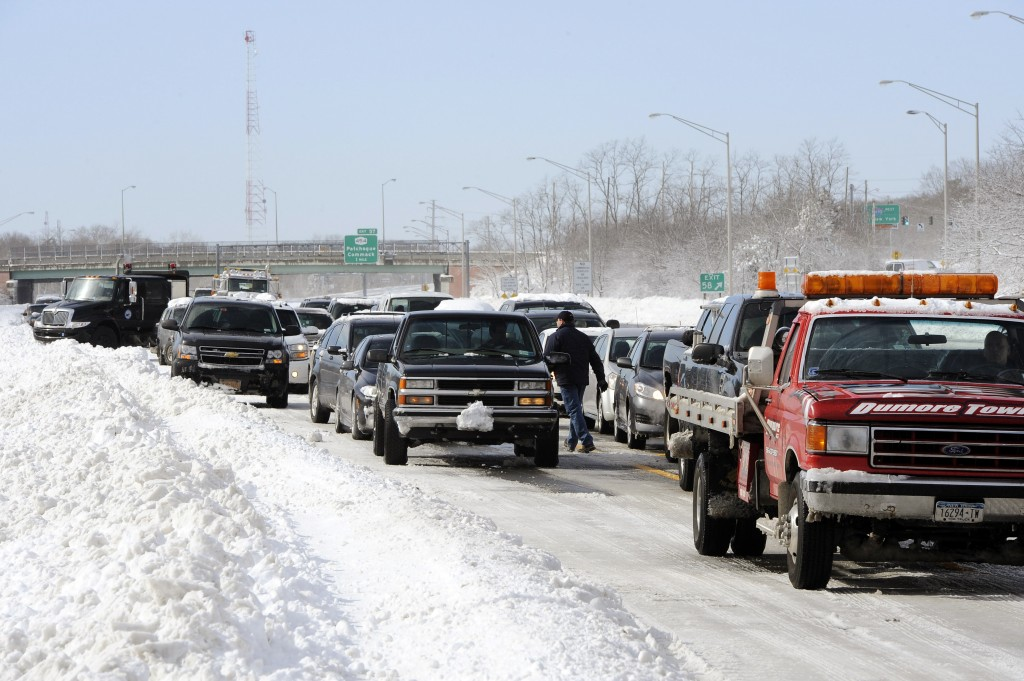 Traffic is backed up on the Long Island Expressway just west of Exit 59 Ocean Avenue as payloaders clear snow from the road after a storm, in Ronkonkoma , N.Y. (AP Photo/Kathy Kmonicek)