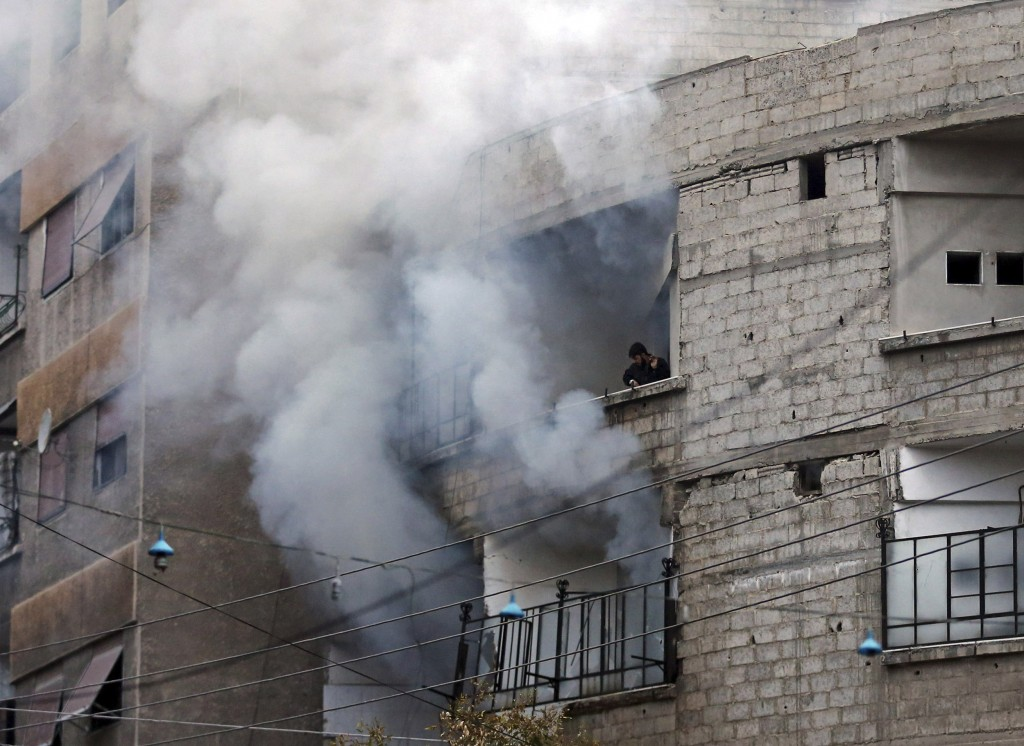 A man tries to extinguish a fire from a balcony in a burning building hit by a mortar shell fired by Syrian Army soldiers, in the Zamalka neighbourhood of Damascus Thursday. (REUTERS/Goran Tomasevic)