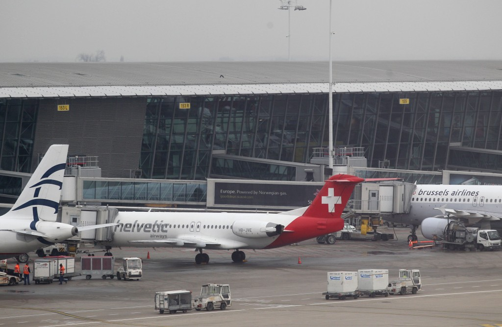 Baggage carts make their way past a Helvetic Airways aircraft from which millions' of dollars worth of diamonds were stolen on the tarmac of Brussels International Airport, Tuesday. (AP Photo/Yves Logghe)