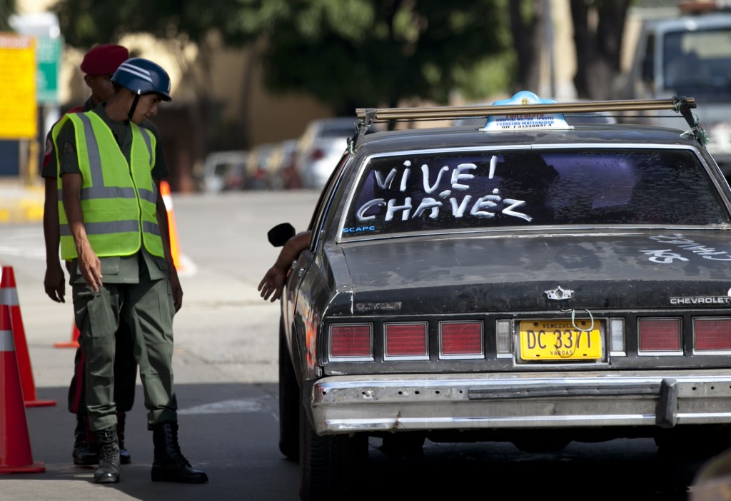 "A National Guard soldier stops a driver whose taxi cab has a message on the back window that reads in Spanish, ""Chavez is alive!"" at the entrance of the Military Hospital where Chavez is allegedly receiving treatment in Caracas, Venezuela, Thursday. (AP Photo/Ariana Cubillos)"