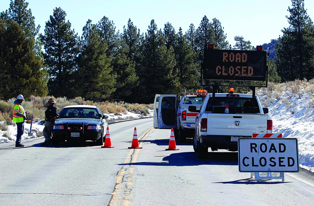 A law enforcement officer stands by a roadblock at Route 38 near Big Bear, Calif., on Wednesday. (AP Photo/Nick Ut)