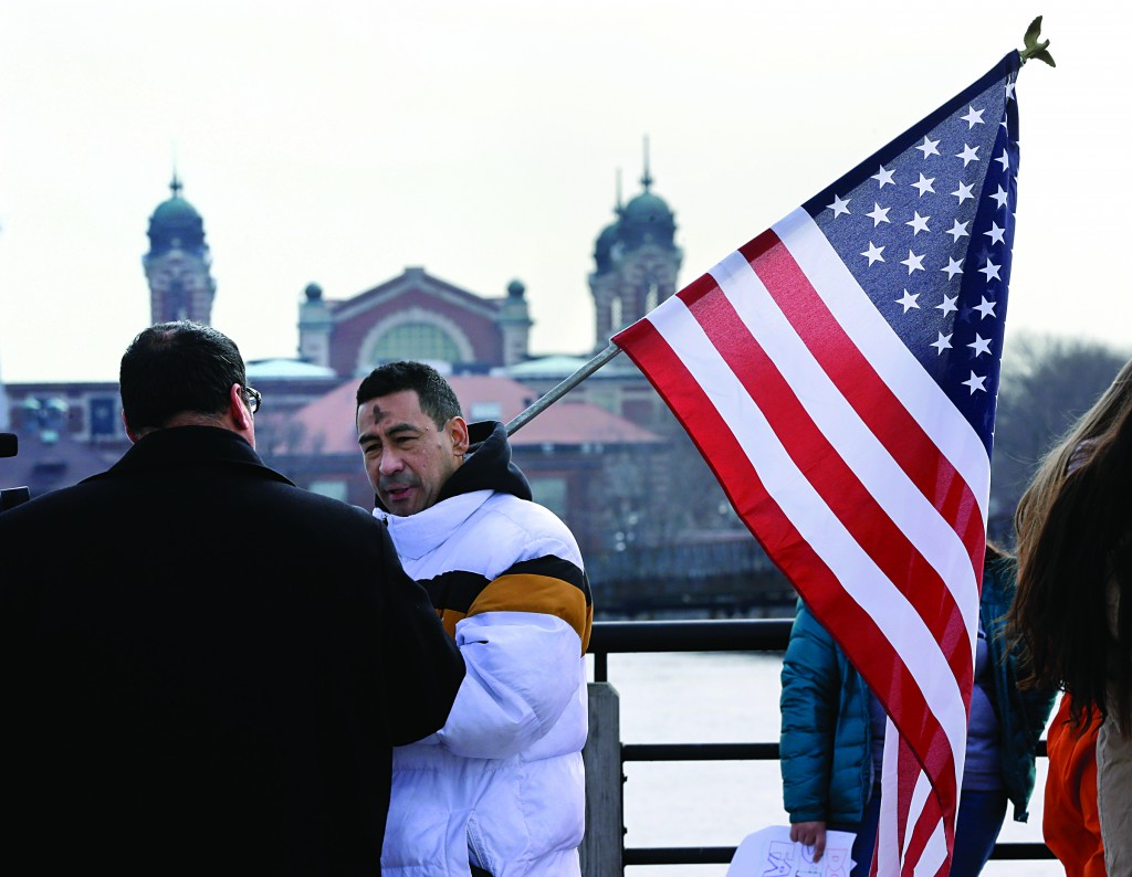 With the Ellis Island behind them, David Toledo, of Peru, holds an American flag, as a group of immigrant rights advocates gather across from Ellis Island Wednesday, in Liberty State Park, Jersey City, N.J. (AP Photo/Mel Evans)