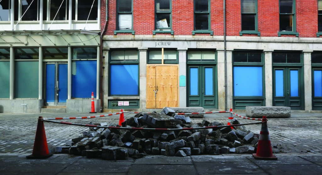 Cobblestones are piled up on Front St. in New York outside the shuttered J. Crew store. Nearly four months after Superstorm Sandy hit, the historic cobblestone streets near the water's edge in lower Manhattan are eerily deserted, and among local business owners, there is a pervasive sense that their plight has been ignored by the rest of Manhattan. (AP Photo/Mary Altaffer)
