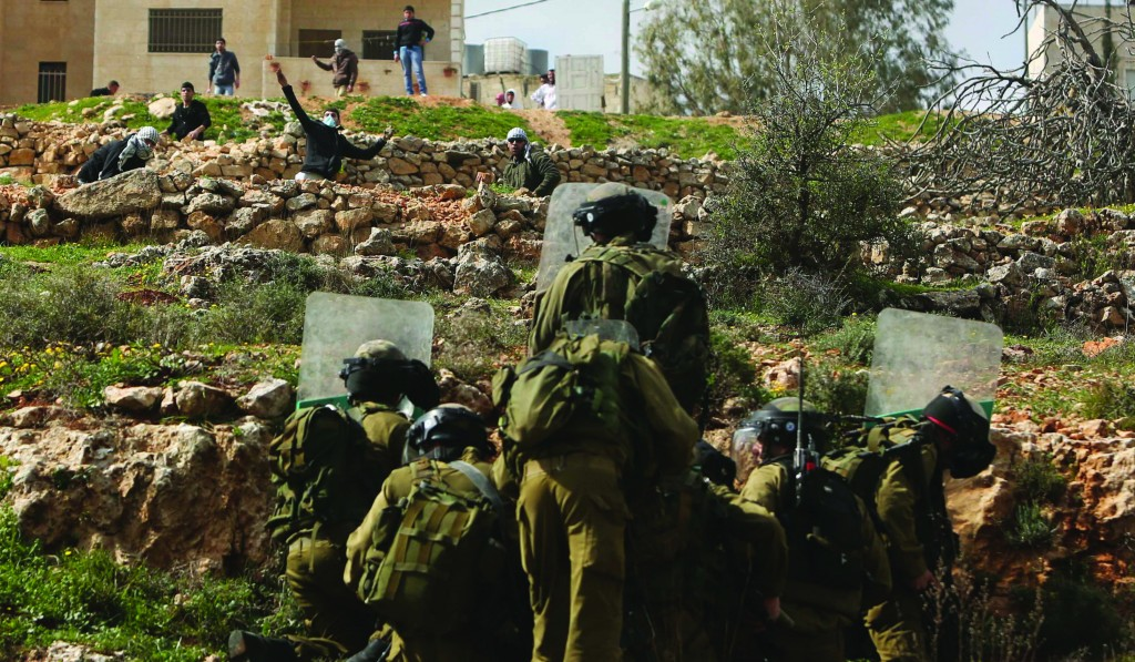 Israeli soldiers take cover behind their shields as a Palestinian protester throws a stone during clashes outside Israel's Ofer Prison near Ramallah on Friday. (REUTERS)