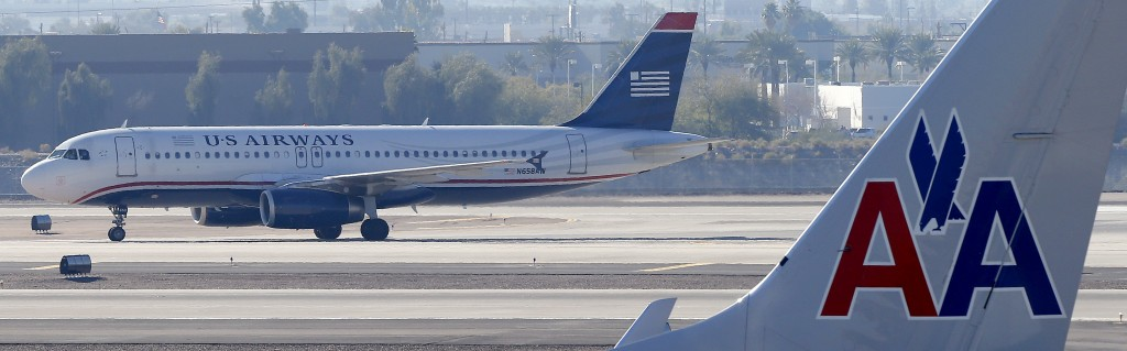 A U.S. Airways jet passes an American Airlines jet, Thursday, Feb. 14, at an airport. The merger of the two airlines will result in a mega-airline with more passengers than any other in the world. (AP Photo/Matt York)