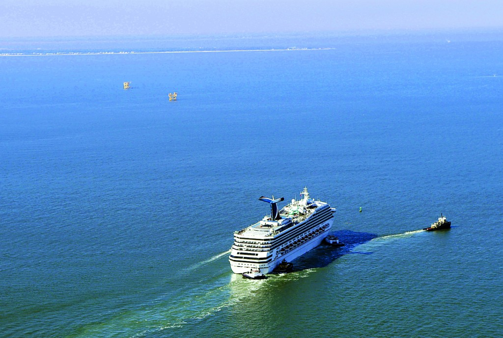 A disabled Carnival Lines cruise ship is towed to harbor off Mobile Bay, Ala., Thursday. (AP Photo/Gerald Herbert)