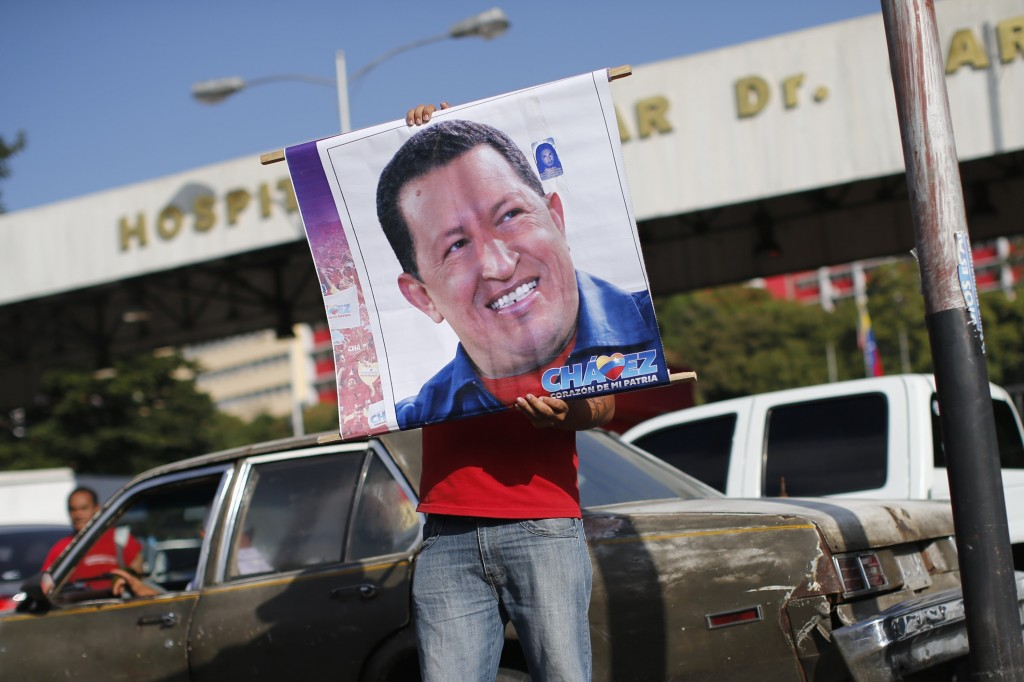 A supporter of Venezuela's President Hugo Chavez holds a poster outside the military hospital after his surprise return to Caracas Monday. (REUTERS/Jorge Silva)