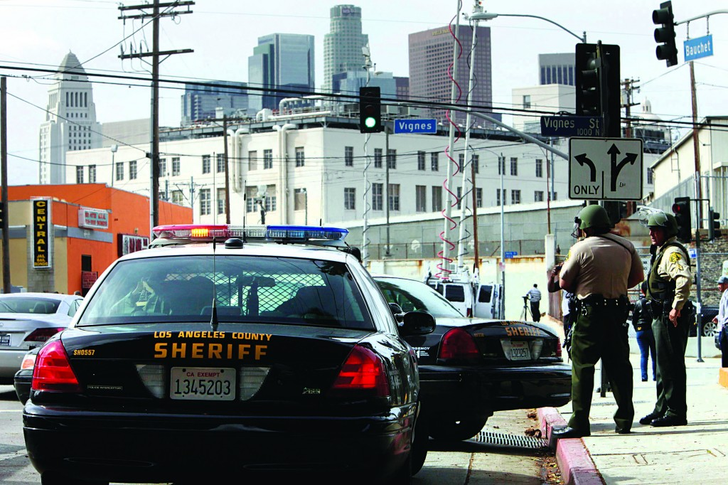 With LA City hall on the horizon, LA County Sheriff Deputies with rifles and shotguns keep watch outside of the Twin Towers Jail in response to a unconfirmed sighting by a civilian employee of Christopher Dorner in Los Angeles. (REUTERS/Patrick Fallon)