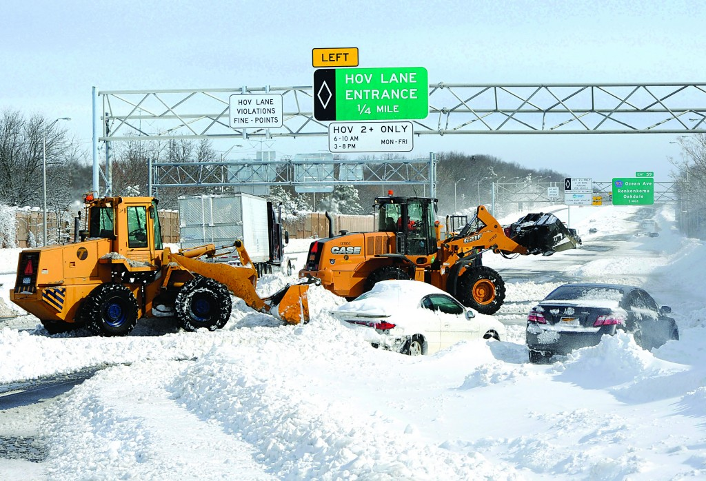 Payloaders clear snow from the Long Island Expressway just west of Exit 59, Ocean Avenue, in Ronkonkoma, N.Y. (AP Photo/Kathy Kmonicek)