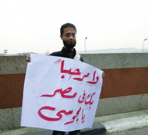 """A man holds a sign in Arabic reading, """"(Ahmedinejad) You are not welcome in Egypt"""", during Ahmedinejad's visit in Cairo Tuesday. (REUTERS/Mohamed Abd El Ghany)"""