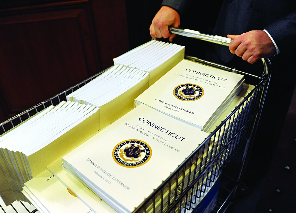 A legislative aide delivers copies of Connecticut Gov. Dannel P. Malloy's budget to the Legislative Office Building in Hartford, Conn., Wednesday. (AP Photo/Jessica Hill)