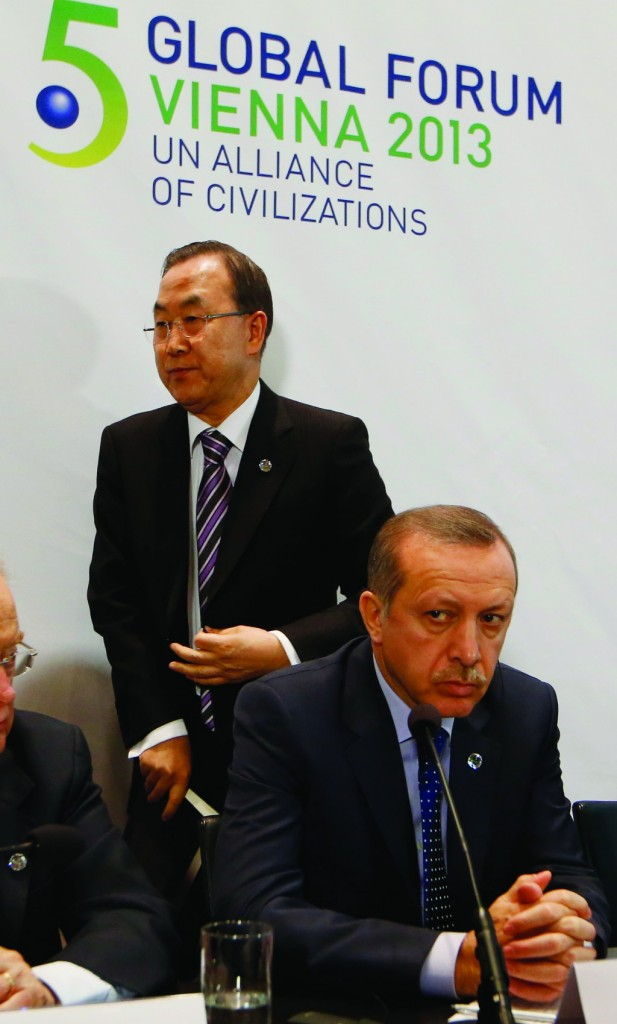 Turkey's Prime Minister Recep Tayyip Erdogan (R) sits at microphone as U.N. Secretary General Ban Ki-Moon walks past during the Fifth Global Forum of the U.N. Alliance of Civilizations in Vienna. (Getty Images)