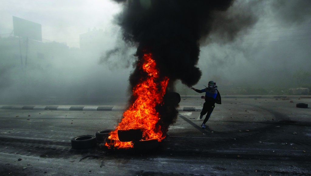 A Palestinian protester throws a tire into a fire during rioting outside Israel's Ofer military prison near Ramallah on Monday. (REUTERS)
