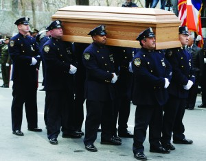 The casket is prepared to be loaded into a hearse as city employees, politicians, media and others look on after his funeral in New York, Monday. (AP Photo/Seth Wenig)