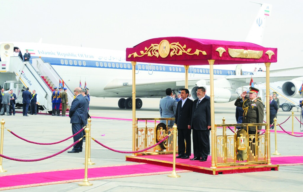 Iran's President Mahmoud Ahmadinejad, center, and Egyptian President Mohammed Morsi, center right, participate in an arrival ceremony at the airport in Cairo, Egypt, Tuesday. (AP Photo/Egyptian Presidency)