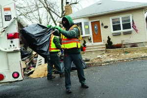 Sanitation workers throw out debris from a flood-damaged home in Oakwood Beach in Staten Island on Tuesday. (Spencer Platt/Getty Images)