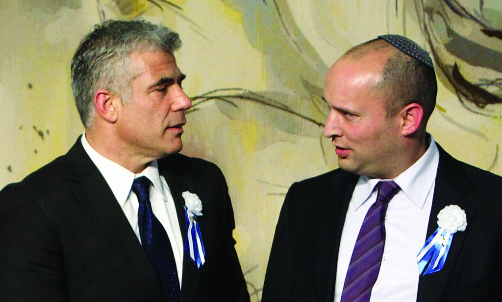 Leader of the Yesh Atid party Yair Lapid (L) seen with Naftali Bennett, leader of the Jewish Home party, on opening day of the 19th Knesset. (FLASH90)