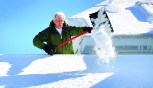 Jim Barrow shovels snow from the roof of his home on Allerton Hill in Hull, Mass., on Sunday. (AP Photo/The Patriot Ledger, Gary Higgins)