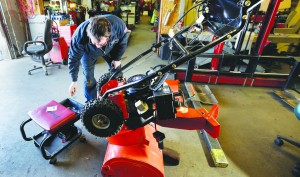Kelly Pomerleau of Andover Small Engine Service repairs a snow blower for a customer in Andover, Mass., Thursday, in preparation for a major winter storm headed toward the U.S. Northeast. (AP Photo/Elise Amendola)