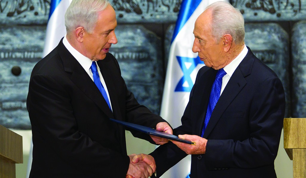 Israeli Prime Minister Binyamin Netanyahu (L) receives a folder from Israeli President Simon Peres in a brief ceremony charging Netanyahu with forming the next government. (AP Photo)