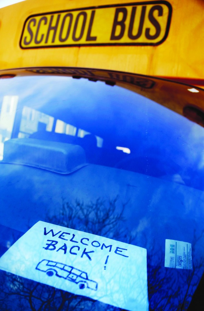A sign made by parents is displayed in the window of Philip Pan's bus while waiting to drop off children at school in New York, Wednesday, Feb. 20. (AP Photo/Seth Wenig)