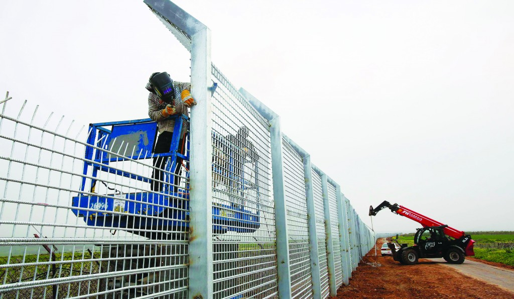 Against a background of civil war in Syria, workers reinforce the fence near Israel's border with Syria in the Golan Heights on Thursday. (REUTERS)