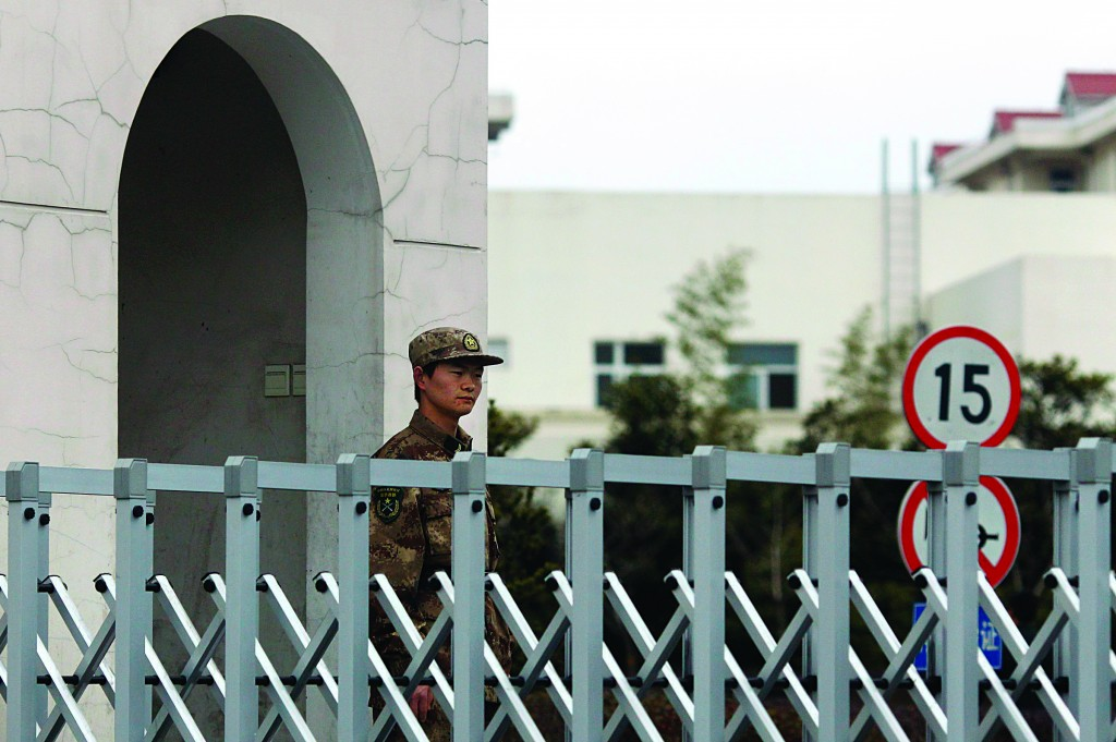 "A Chinese People's Liberation Army soldier stands guard in front of ""Unit 61398,"" a secretive Chinese military unit, in the outskirts of Shanghai, Tuesday. (REUTERS/Carlos Barria)"