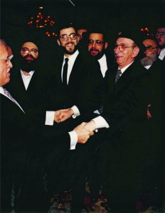 "Rabbi Friedenson (R) dancing with Rabbi Moshe Sherer (L) and, ybl""c, Rabbi Chaim Dovid Zwiebel standing behind in the center."
