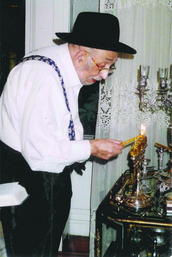 Rabbi Friedenson lighting the menorah.