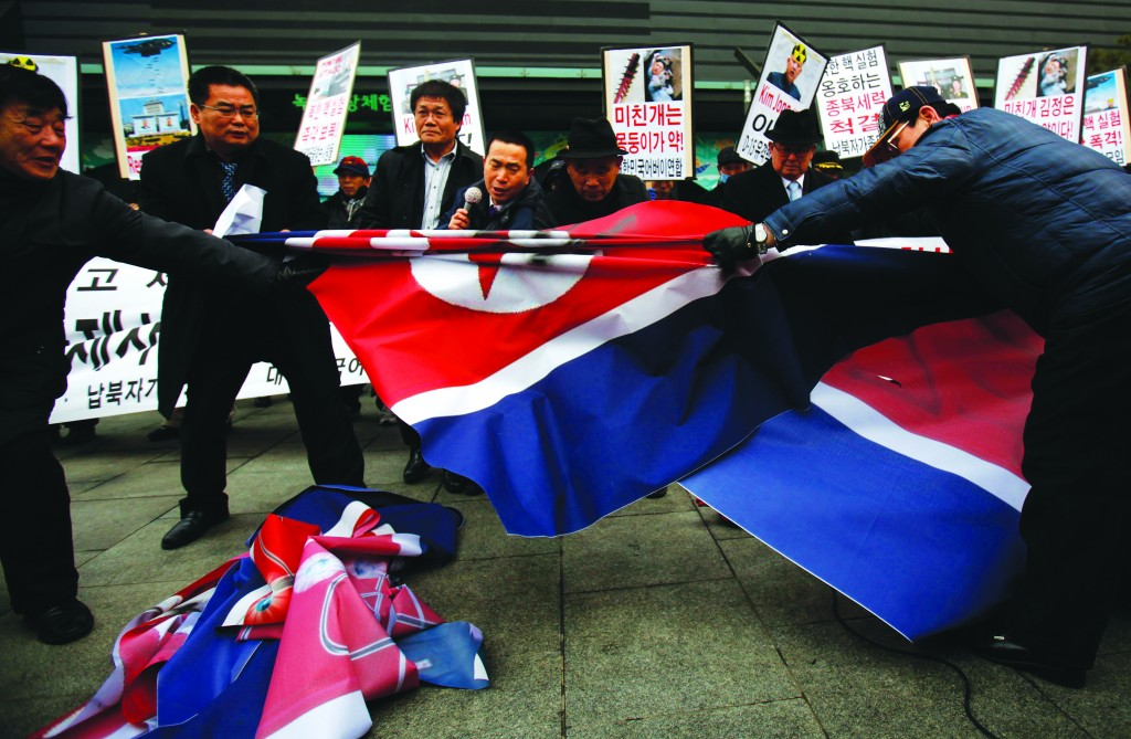 Activists from an anti-North Korea civic group try to tear a North Korea flag near the U.S. embassy in central Seoul, February 12, during a rally against North Korea's nuclear test. (REUTERS/Kim Hong-Ji)