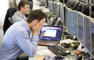 A trader reacts on the IG Group trading floor in London Monday. The surprise decision by euro zone leaders to part-fund a bailout of Cyprus by taxing bank deposits sent shockwaves through financial markets on Monday, with shares and the bonds of struggling euro zone governments tumbling. (REUTERS/Neil Hall)