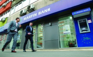People walk past a branch of the Cyprus-based Marfin Bank in Bucharest Tuesday. (REUTERS/Bogdan Cristel)
