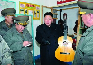 North Korean leader Kim Jong-Un (C) holds a guitar during his visit to a military unit on the Wolnae Islet Defence Detachment in the western sector of the front line, near Baengnyeong Island of South Korea. This photo was taken Monday and was released by the North's official KCNA news agency in Pyongyang. (REUTERS/KCNA)