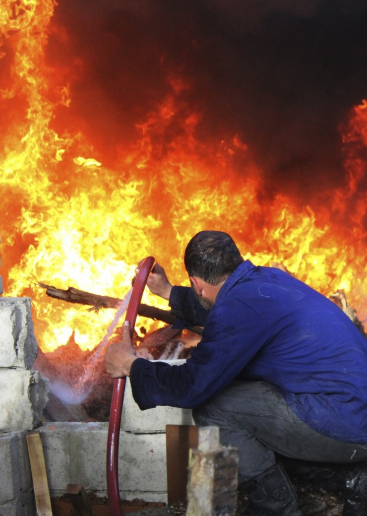 A man tries to extinguish a fire following shelling by forces loyal to Syria's President Bashar al-Assad. (REUTERS/ Mohammed Dimashkia)