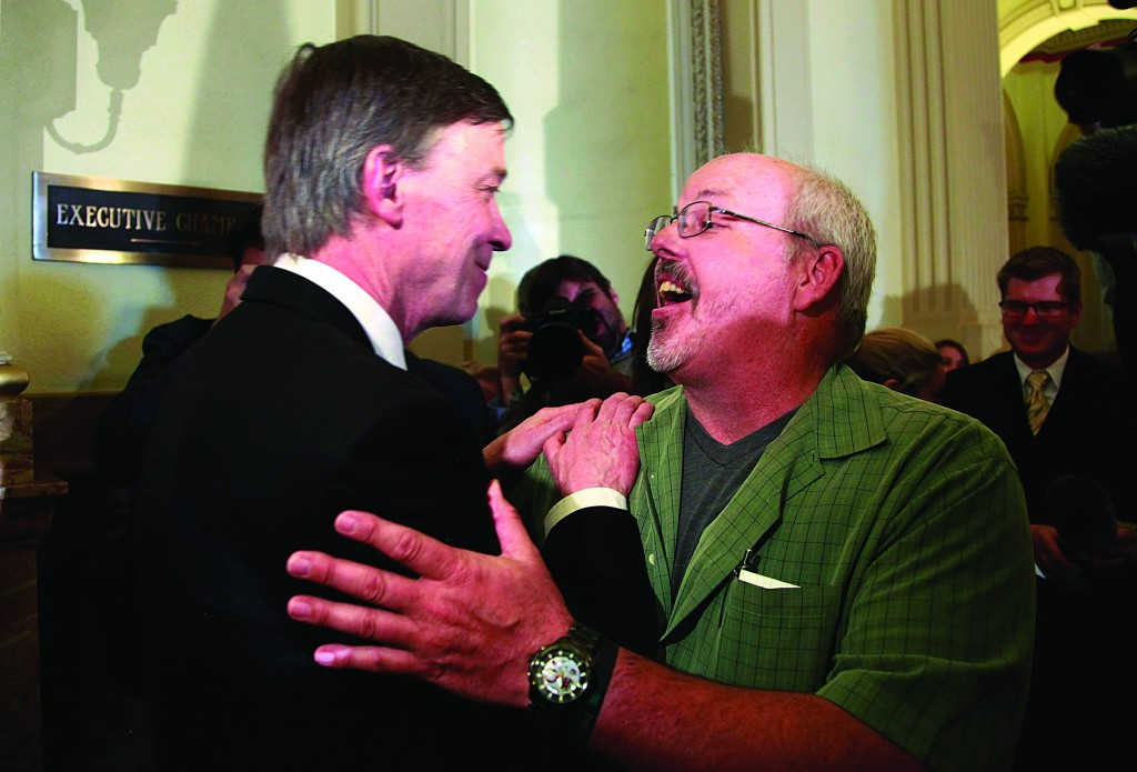 Tom Sullivan (R), whose son Alex was killed in the Colorado theater shootings, embraces Colorado Governor John Hickenlooper after a news conference in Denver Tuesday. (REUTERS/Rick Wilking)