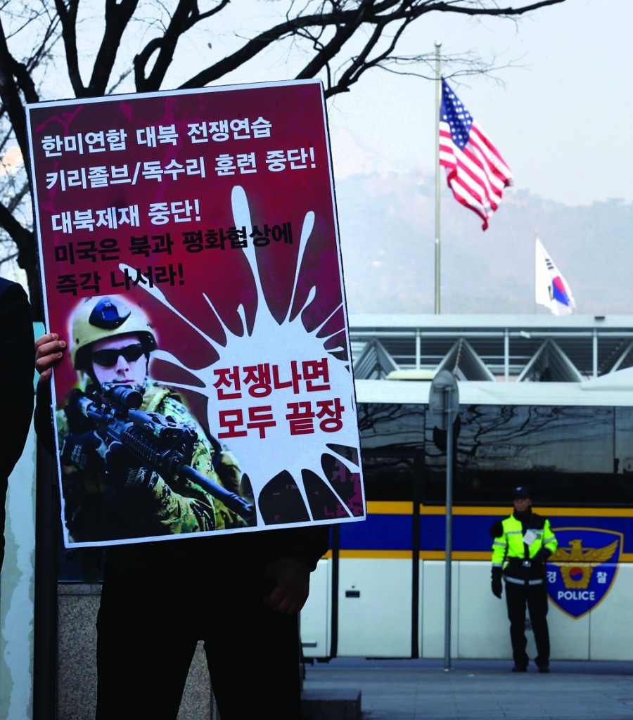 A South Korean protester holds an anti-war sign as a police officer, right, stands guard during a rally denouncing the annual joint military exercises, dubbed Key Resolve and Foal Eagle, between South Korea and the United States, near the U.S. Embassy in Seoul, South Korea, Tuesday. (AP Photo/Lee Jin-man)