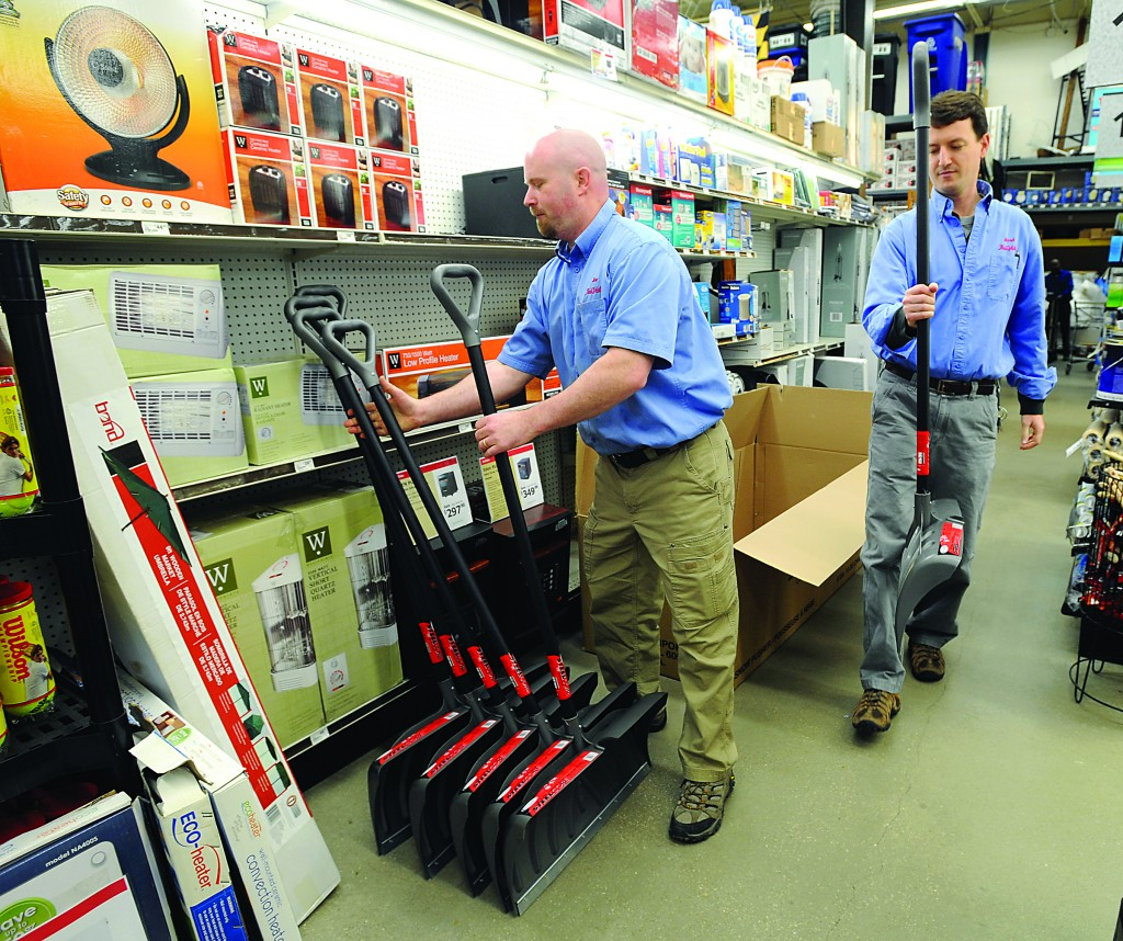 Store manager Joe Hogbin (L) and store owner Jared Littmann un-box more snow shovels to bring to the front of the K&B True Value store in Annapolis, Md. The coming possibility of a late winter snowstorm has people heading to the store, in Bay Ridge, for supplies like snow shovels and ice melt. (AP Photo/The Capital Gazette,Paul W. Gillespie)