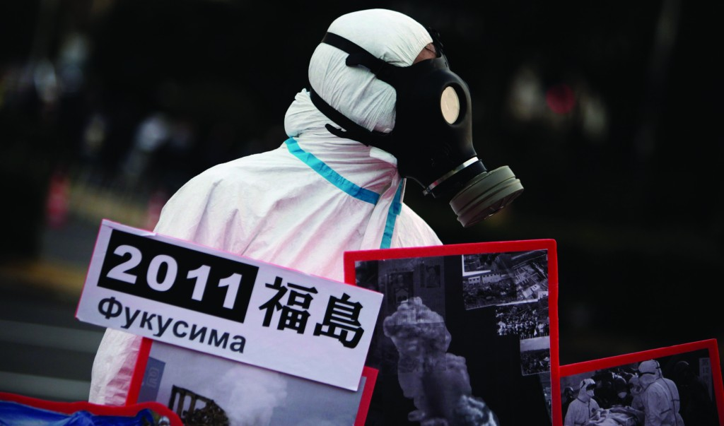 A man in a protective suit and mask holds placards illustrating nuclear disaster in Fukushima during an anti-nuclear demonstration in Tokyo Sunday. (AP Photo/Junji Kurokawa)
