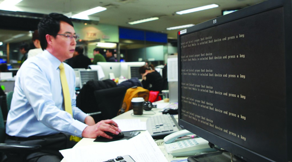 An employee works near a computer screen with error message at the newsroom of the all-news cable channel YTN as the broadcaster's computer network was paralyzed in Seoul, South Korea, Wednesday. (AP Photo/Yonhap)