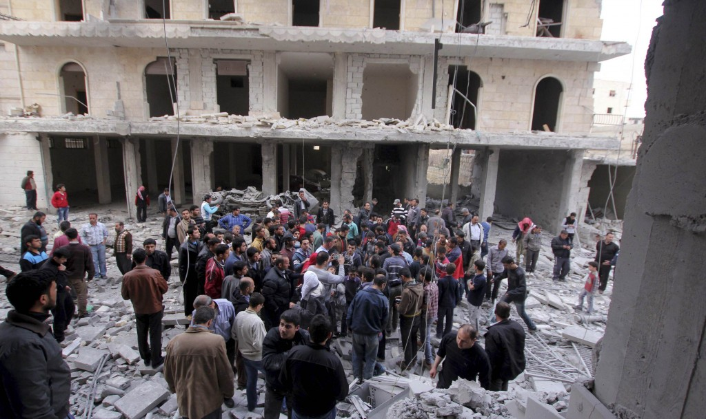 Civilians inspect a building, which activists said was damaged after going under fire by a Syrian Air Force fighter jet loyal to Syria's President Bashar al-Assad, in Kefr Hamra area, north of Aleppo. (REUTERS/Giath Taha)