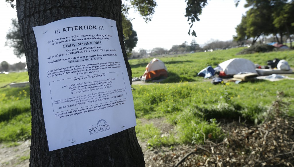 An eviction notice posted by San Jose city workers is shown on a tree at a tent city in San Jose, Calif. (AP Photo/Jeff Chiu)