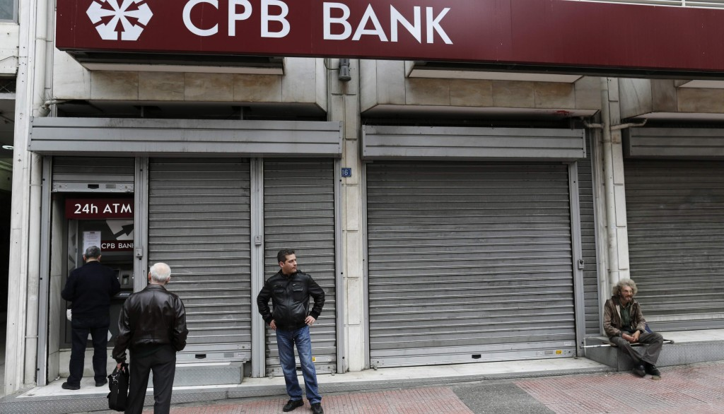 People wait to make transactions at an ATM machine at a closed Cyprus Popular Bank (CPB) branch in Athens Thursday. (REUTERS/John Kolesidis)